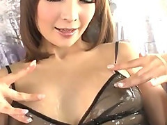 Riona Suzune is oiled up while she plays with her nipples and shaved pussy