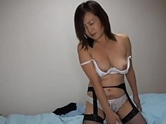 Hot Japanese MILF in fishnets gets toyed on a bed